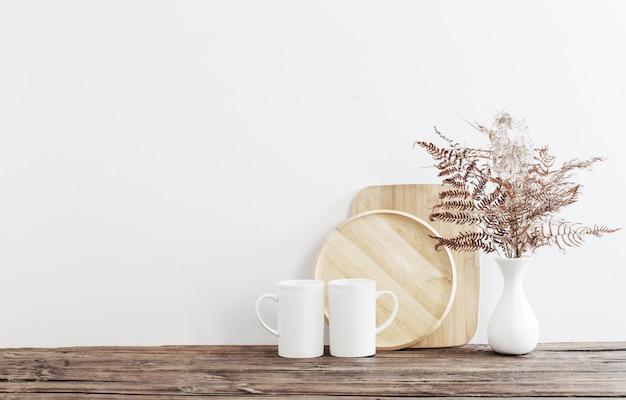 Twee kopjes en gedroogde bloemen op witte keuken