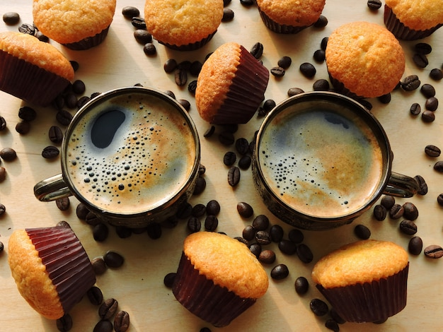 Twee kopjes espresso, mini-muffins, koffiebonen.