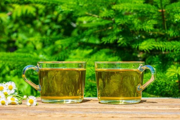 Twee kopjes groene thee en een bosje kamille op een tafel close-up