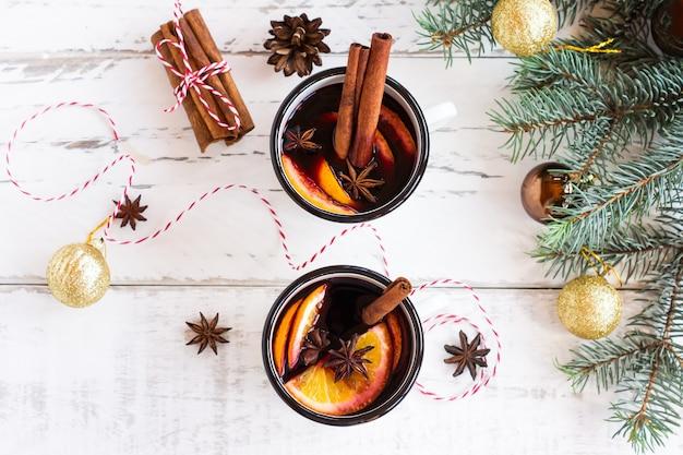 Twee kopjes herfst glühwein of gluhwein met kruiden en stukjes sinaasappel op rustieke tafelblad weergave. traditioneel drankje op herfst- en wintervakantie.