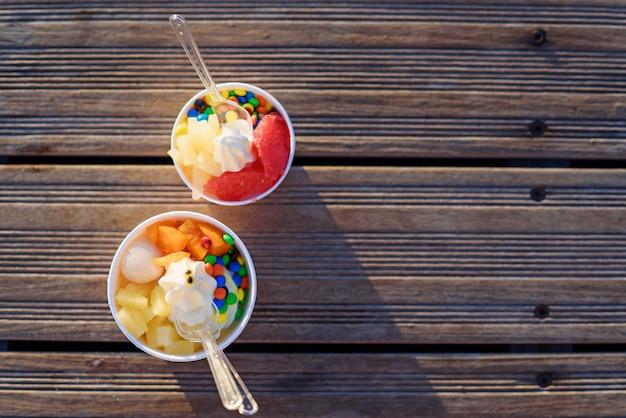 Twee kopjes ijs met snoepjes op zonsondergang.