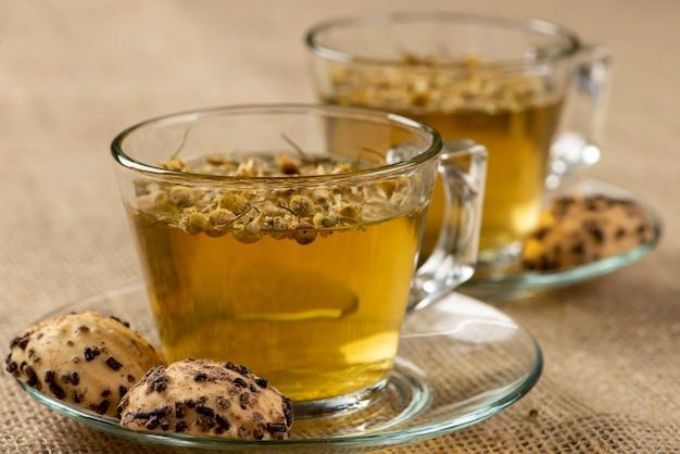 Twee kopjes kamille thee met zoete wafel.