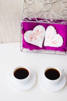 Twee kopjes koffie en koekjes in de vorm van een hart op een roze servet
