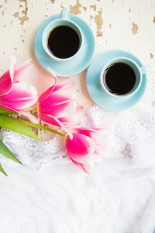Twee kopjes koffie en roze tulpen op een oude tafel