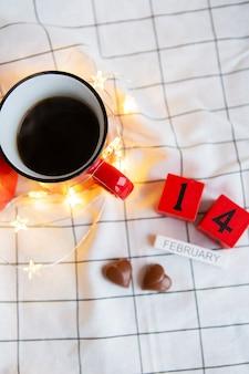 Twee kopjes koffie in rode kopjes op een tafel met chocoladehartjes. ochtendverrassing voor valentijnsdag. uitzicht van boven.