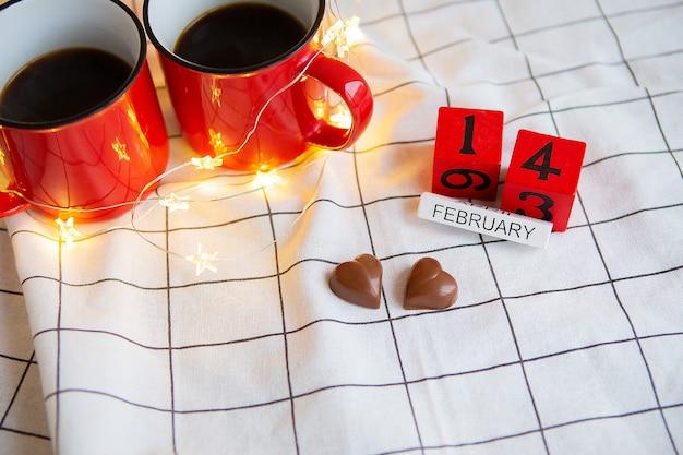 Twee kopjes koffie in rode kopjes op een tafel met chocoladehartjes. valentijnsdag ochtendverrassing.