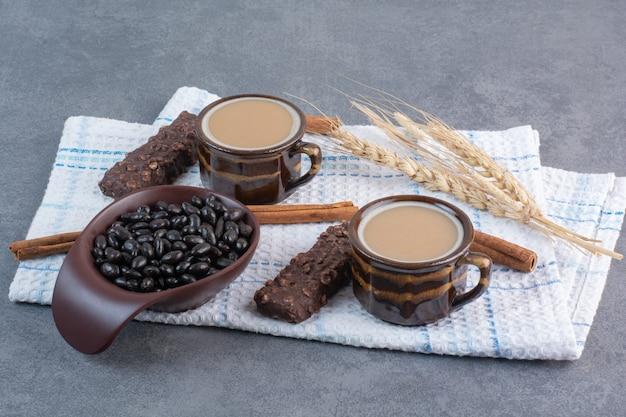 Twee kopjes koffie met een vel papier en chocolaatjes op tafellaken.