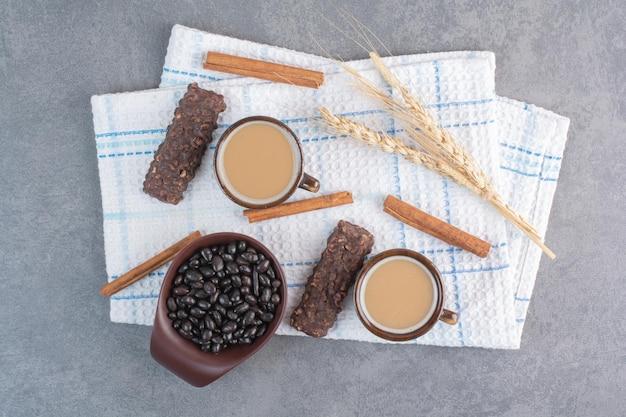 Twee kopjes koffie met een vel papier en chocolaatjes op tafellaken
