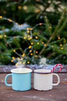 Twee kopjes koffie met kerstverlichting en pijnboom