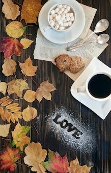 Twee kopjes koffie met koekjes met herfst gekleurde bladeren.