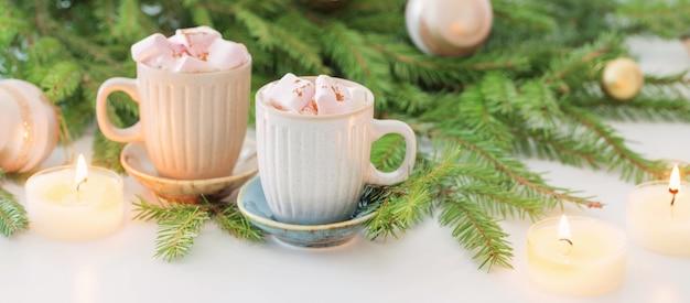 Twee kopjes koffie met marshmallow en kerstspar takken