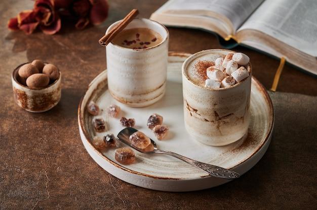 Twee kopjes koffie met schuim en marshmallow en gesublimeerde frambozen met kaneel op lichte plaat