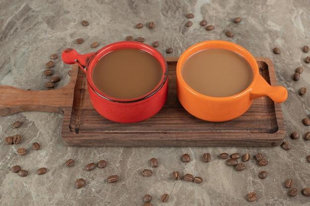 Twee kopjes koffie op een houten bord met koffiebonen.