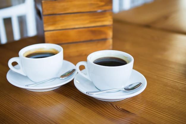 Twee kopjes koffie op een houten tafel, een plek voor tekst.