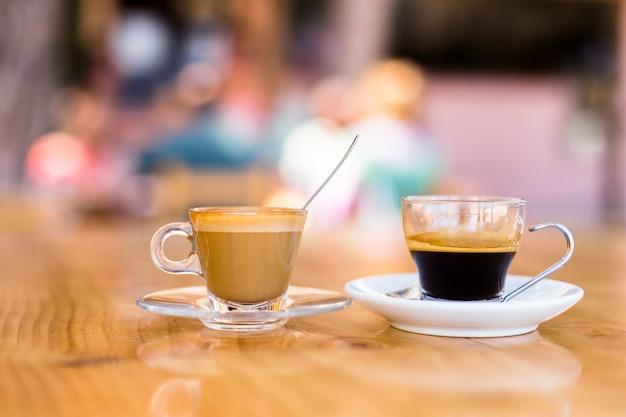 Twee kopjes koffie op een houten tafel in een terras.