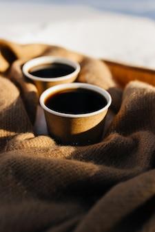 Twee kopjes koffie op een sjaal in het besneeuwde bos