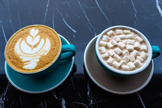 Twee kopjes koffie op een zwarte tafel