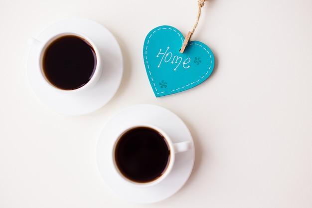 Twee kopjes koffie op tafel en een hart
