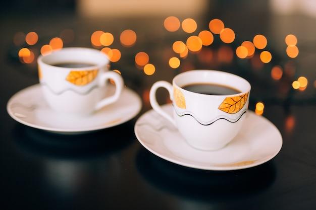 Twee kopjes koffie op tafel met wazige lichten