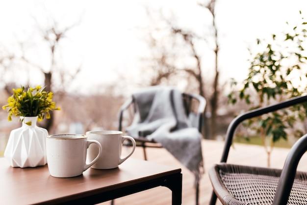 Twee kopjes koffie op tafel op het houten bruine terras tijdens avondzonsondergang. ontspanning, romantisch avondconcept voor geliefden