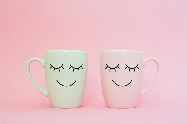Twee kopjes koffie staan samen om hart vorm op roze achtergrond met glimlach gezicht