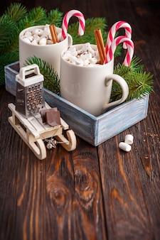 Twee kopjes met kleine marshmallows op een donkere houten achtergrond