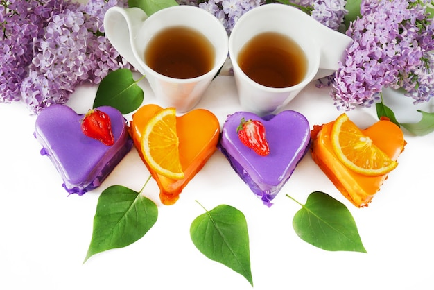 Twee kopjes met thee lila bloemen en cheesecakes leeg voor menu