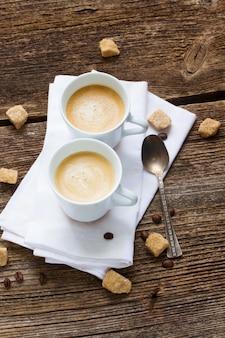 Twee kopjes met verse espresso op houten tafel