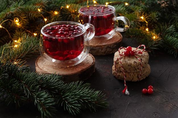 Twee kopjes met warme kerstkruidige drank met cranberry en gebak. kerst concept