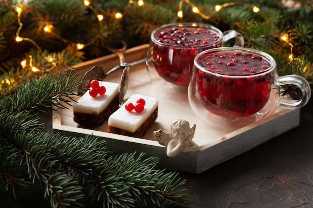 Twee kopjes met warme kerstkruidige drank met cranberry en gebak
