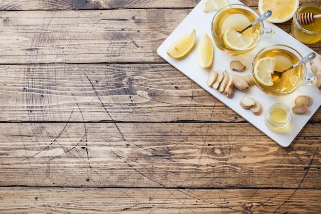 Twee kopjes natuurlijke kruidenthee gember citroen en honing op een houten oppervlak.