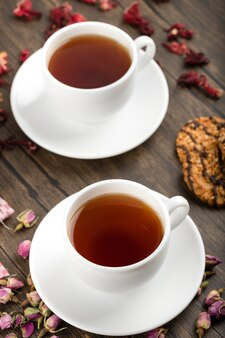 Twee kopjes thee, bloemen en havermoutkoekjes op houten oppervlak