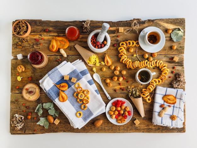 Twee kopjes thee, diverse soorten jam en andere zoetigheden op de oude houten tafel.
