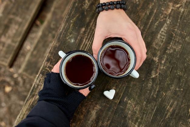 Twee kopjes thee in de natuur in de handen van paar in zwarte handschoenen op houten oppervlak