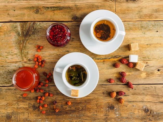 Twee kopjes thee, jam en gedroogd fruit op een oude houten tafel.
