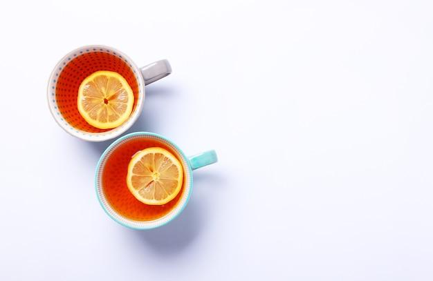 Twee kopjes thee met citroen op witte achtergrond. bovenaanzicht, plat leggen. kopieer ruimte. thee voor herfst- of winterseizoen.