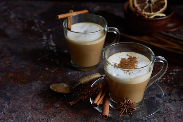 Twee kopjes warme cappuccino-koffie met kaneel en anijs op een bruine ondergrond