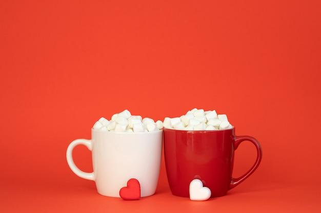 Twee kopjes witte en rode kleuren met cacao en marshmallows. valentijnsdag of liefde concept.