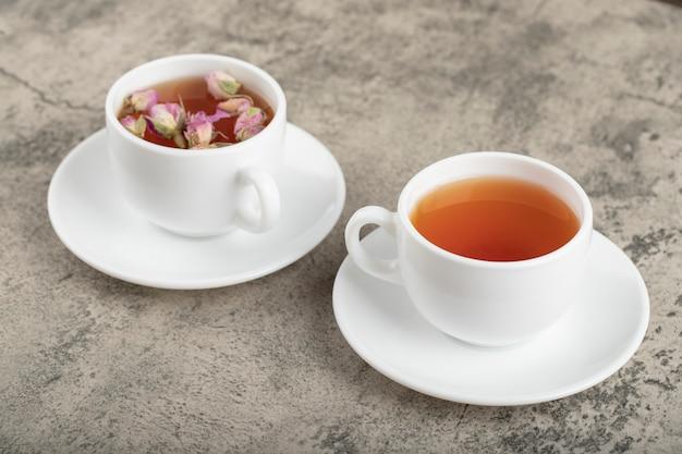 Twee kopjes zwarte thee met gedroogde rozen op stenen oppervlak.