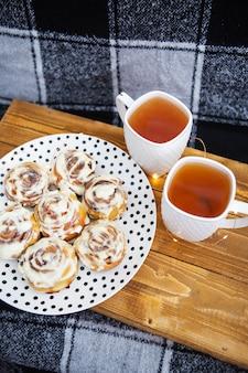Twee kopjes zwarte thee staan op een houten dienblad op de bank met een zwart-wit geruite plaid. de verse en geurige kaneelbroodjes sluiten omhoog liggen op een bord met stippen, mooie ochtend