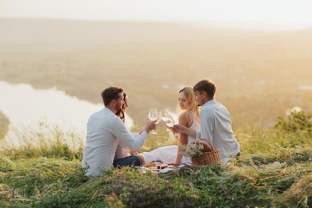 Twee koppels die wijn drinken tijdens een picknick in een veld