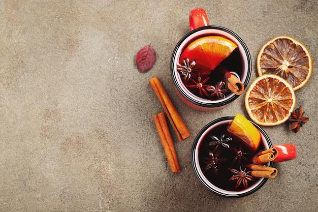 Twee koppen kerstmis overwogen wijn of gluhwein met kruiden en oranje plakken op rustieke lijst