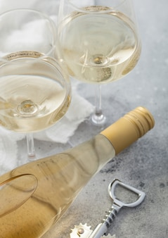 Twee kristallen glazen en fles witte zelfgemaakte wijn met stalen kurkentrekker op lichte tafel achtergrond.
