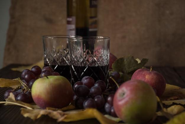 Twee kristallen glazen met rode wijn, appels, druiven en droge bladeren op een houten ondergrond