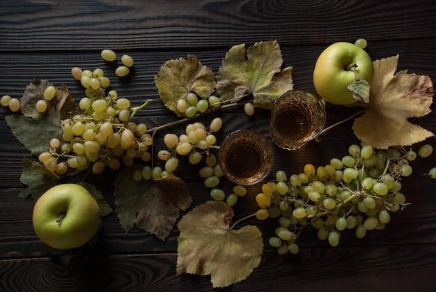 Twee kristallen glazen met witte wijn, appels, druiven en droge bladeren op een houten ondergrond. bovenaanzicht