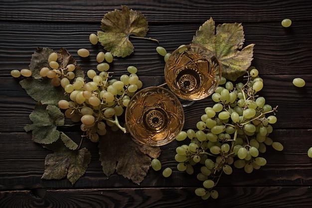 Twee kristallen glazen met witte wijn, druiven en droge bladeren op een houten ondergrond. bovenaanzicht