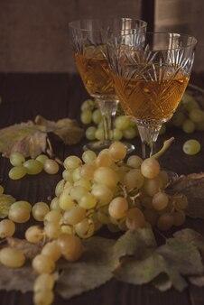 Twee kristallen glazen met witte wijn, druiven en droge bladeren