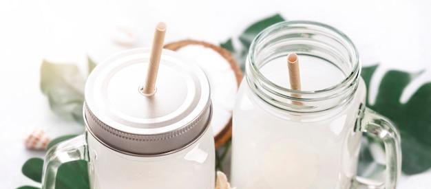 Twee kruiken kokosmelk of niet-alcoholische cocktail sluiten omhoog op wit