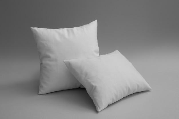 Twee kussens tegen een grijze achtergrond.