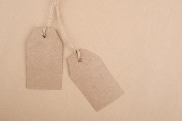 Twee labels van gerecycled kraftpapier die aan een touw op kraftpapier hangen. plat leggen